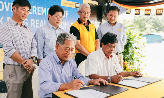 Sales Director of Tractors Malaysia, Azlan Ismail (seated right) and Datuk Toh Chiew Hock, Managing Director of Hock Peng Group (seated left) inking the deal at the signing ceremony.